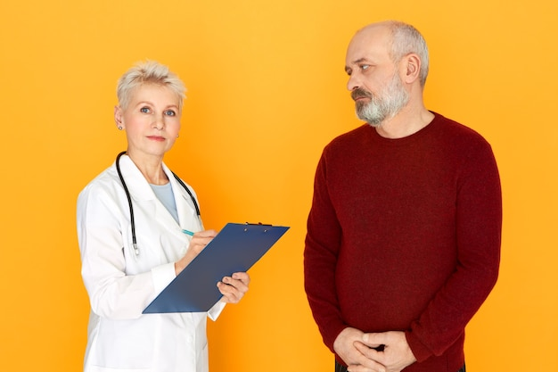 Successful serious mature woman practitioner in white coat checking health condition with her elderly male patient during physical examination, holding clipboard and pen, looking at camera