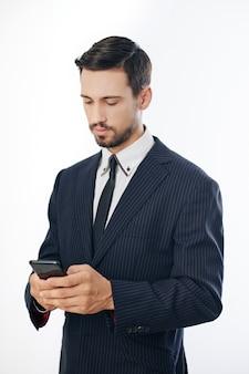 Успешный серьезный молодой предприниматель в костюме читает текстовые сообщения коллег на смартфоне