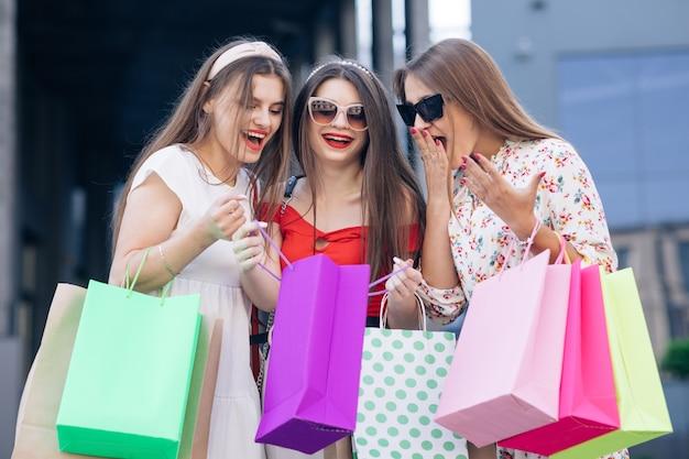 Удачных покупок. повседневный макияж. группа молодых счастливых симпатичных женщин в повседневных платьях, топе и брюках, идущих от здания с желтыми, зелеными, фиолетовыми и розовыми сумками в руках.