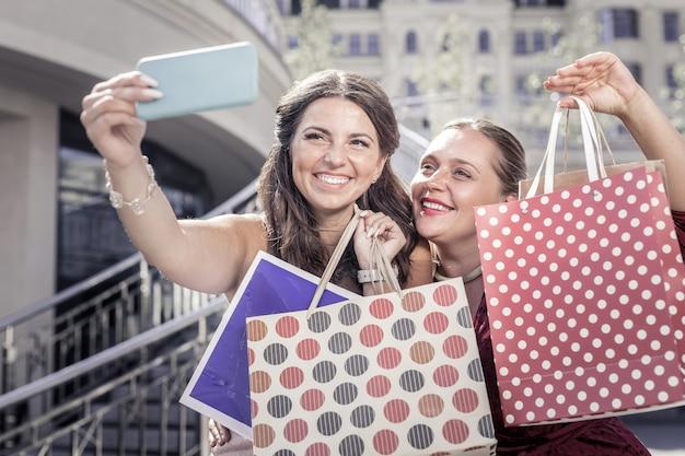成功した買い物。一緒に写真を撮りながらバッグを見せて幸せな喜びの女性