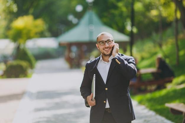 白いシャツ、クラシックなスーツ、メガネで成功したスマートビジネスマン。男はラップトップpcコンピューターで立って、自然の背景に屋外の都市公園で携帯電話で話します。モバイルオフィス、ビジネスコンセプト。