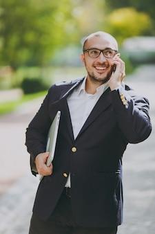 흰 셔츠, 고전적인 양복, 안경을 쓴 성공적인 똑똑한 사업가. 남자는 노트북 컴퓨터와 함께 서서 자연 배경의 야외 도시 공원에서 휴대 전화로 이야기합니다. 모바일 오피스, 비즈니스 개념입니다.