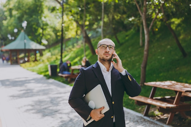 Successful smart businessman in white shirt, classic suit, glasses. man stand with laptop pc computer, talk on mobile phone in city park outdoors on nature background. mobile office, business concept.