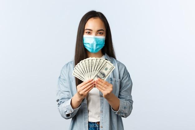 Успешная улыбающаяся азиатская женщина зарабатывает деньги, показывая наличные доллары, надевает медицинскую маску, работая дома