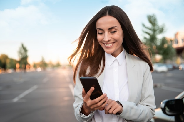 공식적인 스마트 웨어를 입은 성공적인 웃는 매력적인 여성이 야외에서 현대적인 자동차 근처에 서 있는 동안 스마트 폰을 사용하고 있습니다