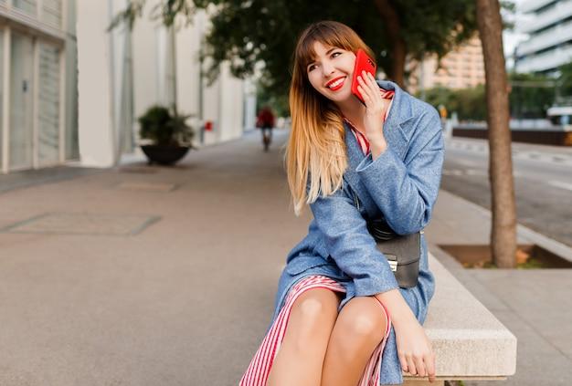 Femmina bionda sorridente riuscita che parla dal telefono cellulare sul fondo urbano dopo il lavoro. seduto su una panchina.
