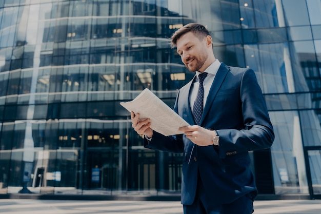 Successful smiling business owner in blue suit reading good news in newspaper and smiling while standing outside alone with glass office building behind him, walking during work break outdoors
