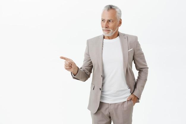 Riuscito uomo d'affari sorridente che indica il dito a sinistra
