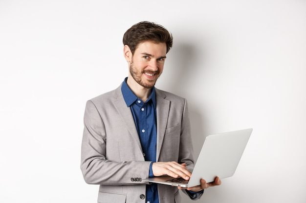Successful smiling businessman working on laptop and looking happy at camera, standing in grey suit on white background.