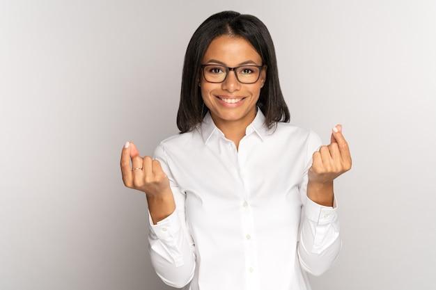 성공적인 웃는 여성 사업가는 투자 지불 급여를 요구하는 손가락으로 돈 제스처를 한다