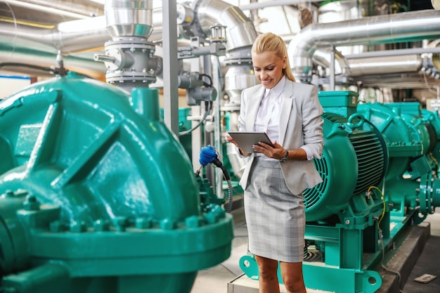 Successful smiling hardworking female manager in suit standing in heating plant with tablet in hands and checking on turbine.