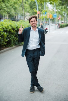 Successful smiling young businessman standing on street showing victory sign