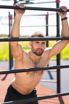 屋外トレーニング中にスポーツバーにもたれながらあなたを見て成功した強力な上半身裸のスポーツマン