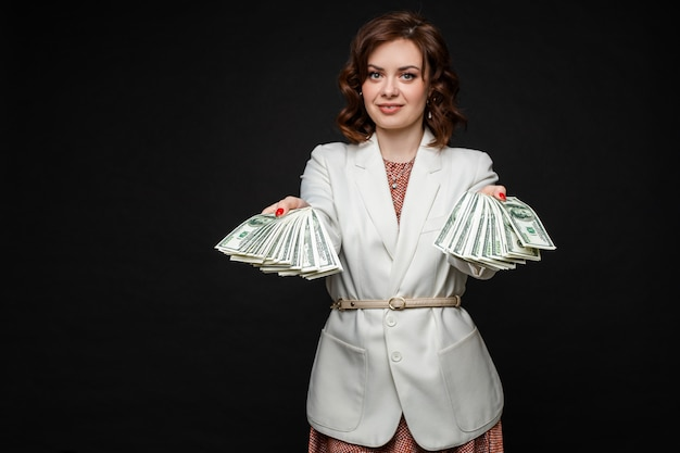 Successful stylish brunette model with money in hands.