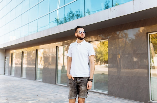 ガラスの建物の壁に白いシャツで成功したスタイリッシュなヒップスター