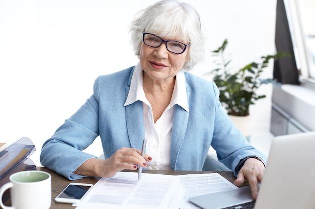 Amministratore delegato femminile maturo elegante di successo che indossa occhiali da vista e abiti formali guardando attraverso la relazione finanziaria, lavorando alla scrivania in ufficio, utilizzando gadget elettronici e prendendo appunti