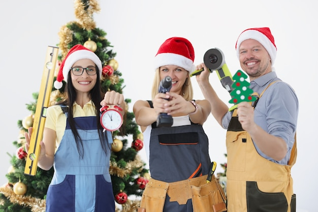 Successful team of builders is holding construction tool against background of the new year