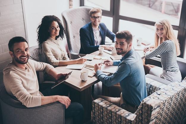 Успешная команда. веселые молодые люди с улыбкой смотрят в камеру, сидя за офисным столом на деловой встрече