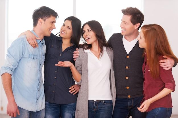 Успешная команда. группа веселых молодых людей, стоящих рядом и общающихся