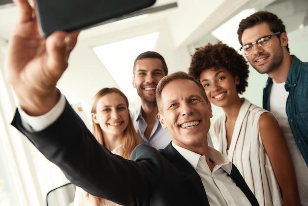 Успешная группа улыбающихся коллег, делающих селфи, стоя в современном офисе