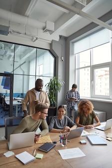Вертикальный снимок успешной команды в коворкинге: многорасовые коллеги общаются и делятся друг с другом