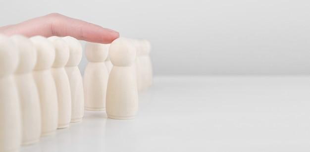 Успешный руководитель команды. рука бизнесмена выбирает людей, выделяющихся из толпы.
