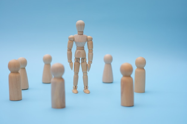 Successful team leader, wooden people standing out from the other.