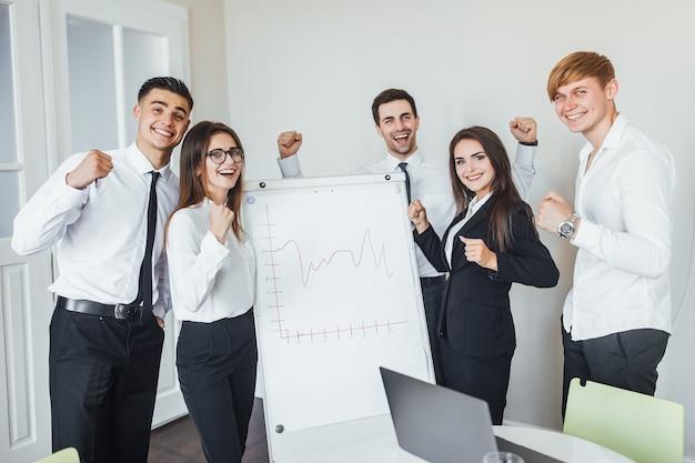 Успешная команда молодых перспективных бизнесменов в офисе после деловой встречи