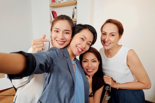 Successful team taking group selfie