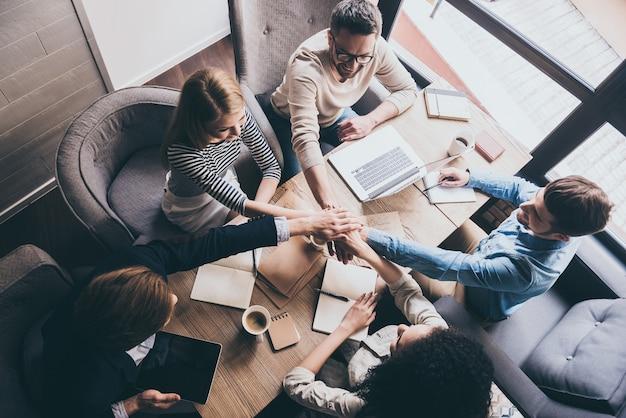 Успешная команда. вид сверху молодых деловых людей, держащихся за руки вместе, сидя за офисным столом вместе