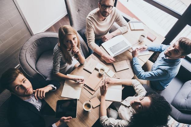 Успешная команда. вид сверху молодых деловых людей, смотрящих в камеру, сидя за офисным столом вместе