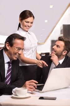 성공적인 팀입니다. 흰색 셔츠를 입은 여성이 컴퓨터 모니터를 가리키는 동안 테이블에 앉아 웃고 있는 정장 차림의 쾌활한 사업가 두 명