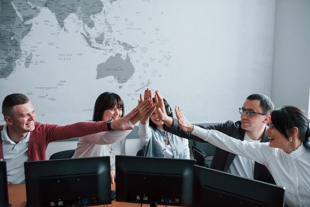 성공적인 팀. 콜 센터에서 일하는 젊은 사람들. 새로운 거래가 다가옵니다