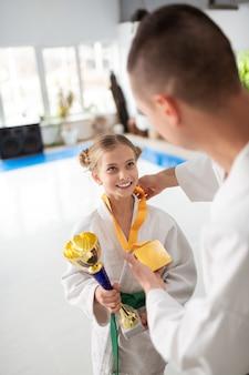 Успешная девочка-подросток, практикующая айкидо, получает призы