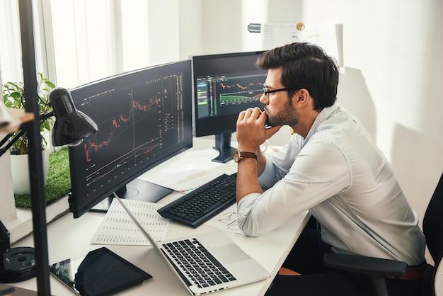 데이터와 그래프를 분석하는 안경을 쓴 수염 난 주식 시장 브로커의 성공적인 트레이더 백 뷰
