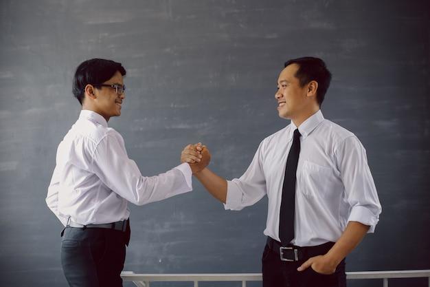 チームの握手をしながら笑顔でシャツとネクタイで成功した2人のアジア人実業家