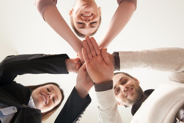 Successful united business team put hands together, view from below