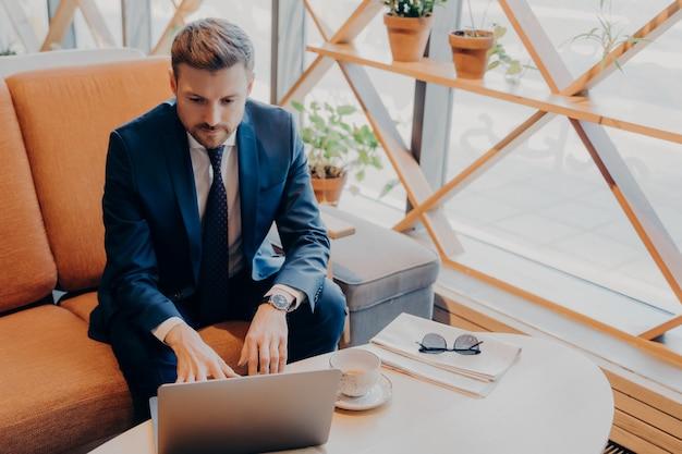 Успешный ухоженный финансист в стильном костюме с подстриженной бородой сидит в вестибюле бизнес-центра за чашкой чая в ожидании встречи и делает последние записи на своем портативном компьютере онлайн.