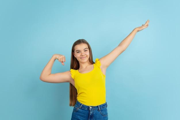 Vincitore di successo. ritratto della ragazza teenager caucasica isolato sulla parete blu. bellissimo modello in abbigliamento casual giallo. concetto di emozioni umane, espressione facciale, vendite, annuncio. copyspace. sembra carino.