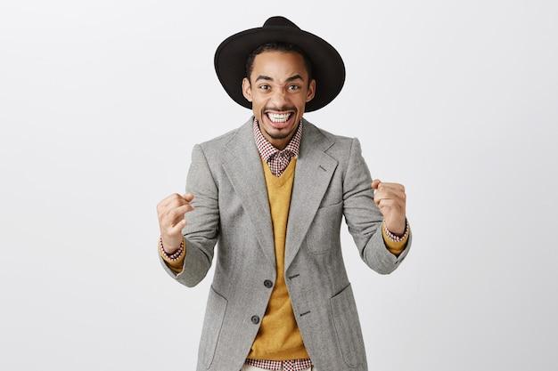 Successo vincente uomo afroamericano in vestito che celebra la vittoria, sorridendo entusiasta e pompa pugno in gioia