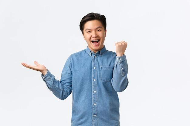 Libero professionista maschio asiatico vincente di successo, pompa pugno ragazzo che tiene qualcosa a portata di mano su uno spazio bianco nero, ottiene l'oggetto, riceve il prodotto che desiderava, celebra o trionfa.