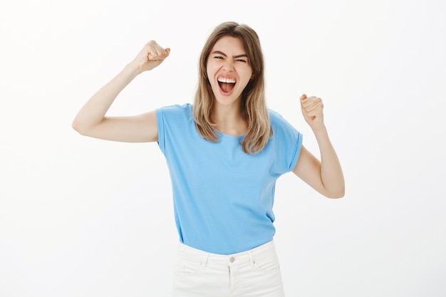 Успешная победа белокурая женщина торжествует, поднимая руки вверх в радости