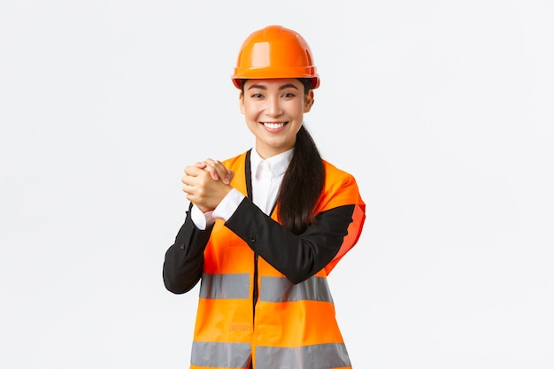 성공적인 우승 여성 아시아 건축가 함께 악수, 목표를 달성. 승리를 축하하는 수석 건설 관리자, 건축 작업 완료, 흰 벽에 서서 기뻐했습니다.