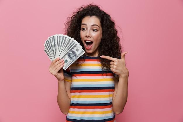 ピンクで隔離されたドルのお金のファンを保持している巻き毛の成功した女性20代