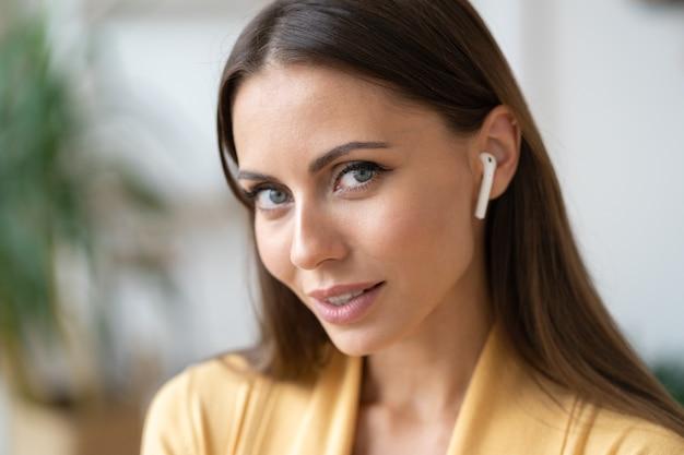 성공한 여성 사업가나 학생은 집에서 화상 통화 회의를 위해 무선 헤드폰을 사용합니다.