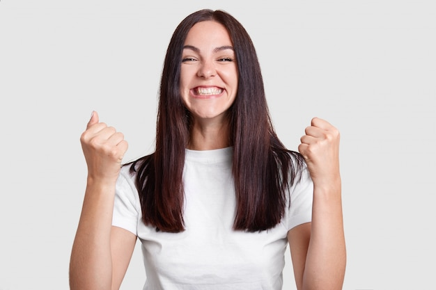 Successful woman clenches fists with happiness, has broad smile, squints face, dressed casual t shirt, isolated over white wall. carefree brunette girl rejoices success. victory, determination