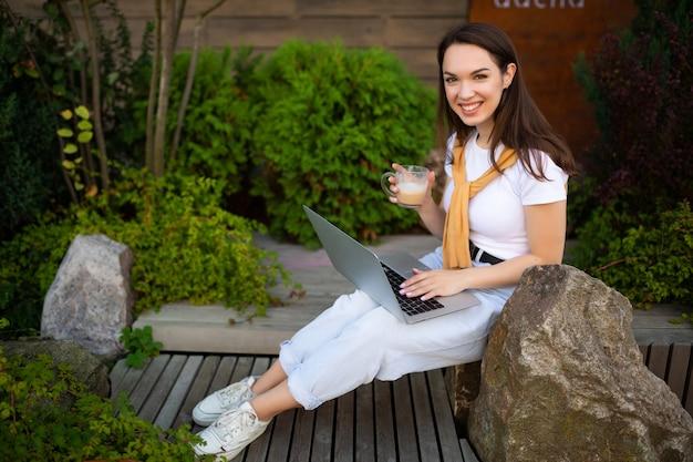 성공적인 여성 프리랜서 귀여운 웃는 앉아 야외에서 컴퓨터.