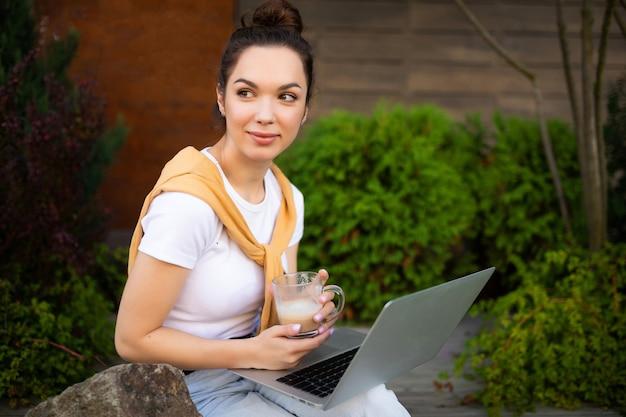 Успешная женщина-фрилансер мило улыбается, сидя на открытом воздухе с компьютером.