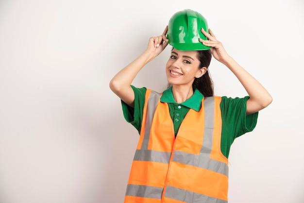 Успешная женщина в каске, носящей униформу. фото высокого качества