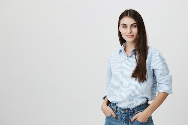 Успешная женщина в рубашке и джинсах с руками в карманах